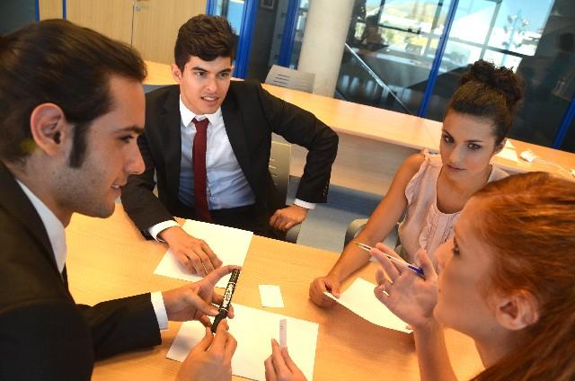 会議室で会話をする4人の男女
