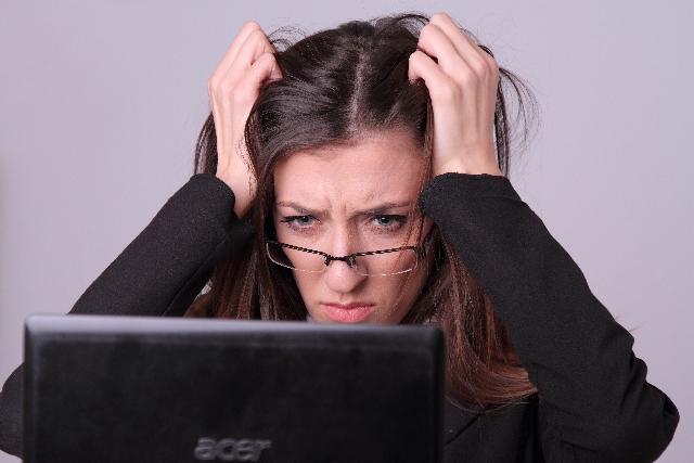 パソコンの画面を見て頭を抱える眼鏡の女性