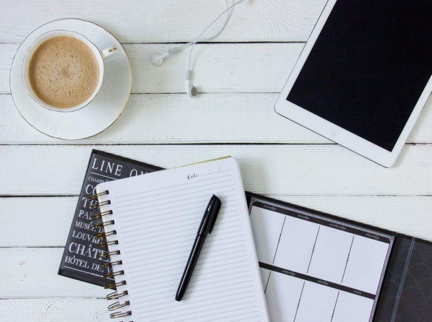 白い木のテーブルに置かれたコーヒーとノートとタブレット
