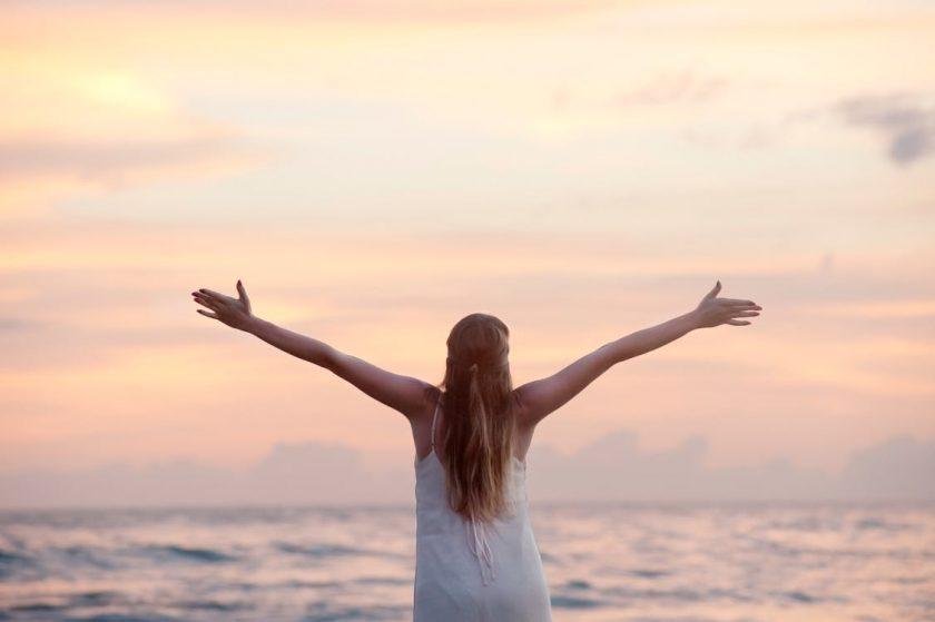 夕暮れの海に向かって両手を広げる女性の後ろ姿