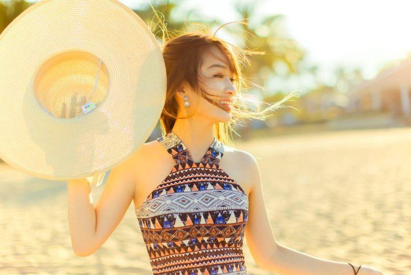 輝く日差しの中で麦わら帽子を手に持つ女性
