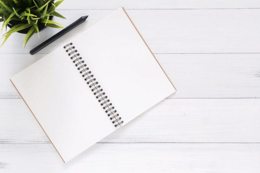 白い木のテーブル上に置かれたノート