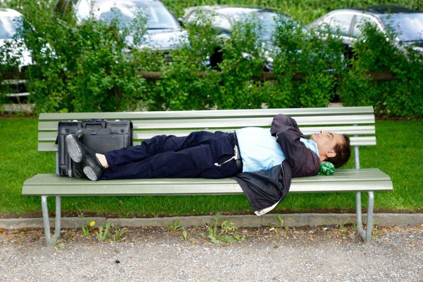公園のベンチに腕を組んで不機嫌そうに寝転がる男性