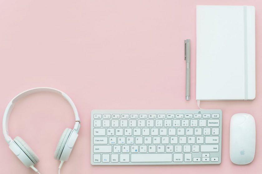 ピンクの台に置かれた白いキーボードとマウスとヘッドホンとノート