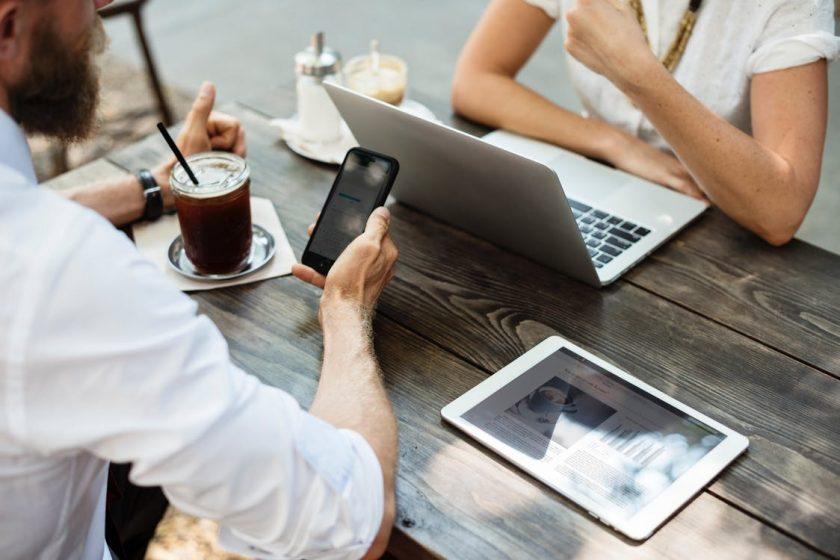 休憩中にノートパソコンとスマホを開いて話し合うビジネスマン