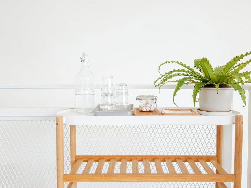 白い部屋のワゴンに乗った植物と水とコップ