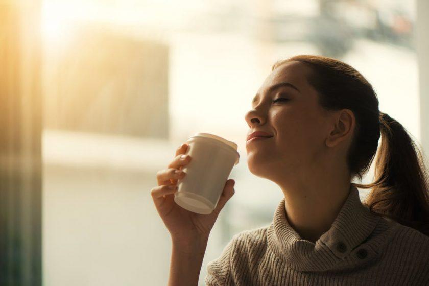 コーヒーを飲んで幸せそうに一息つく女性