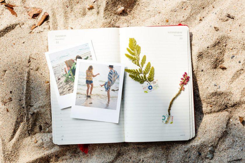 砂浜に置かれたノートと写真