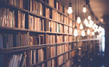 図書館に並んだ本とぶら下がったたくさんの電球
