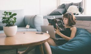 部屋でリラックスしながらノートパソコンを開いて本を読む女性