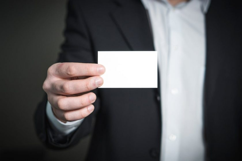 名刺を見せるスーツの男性