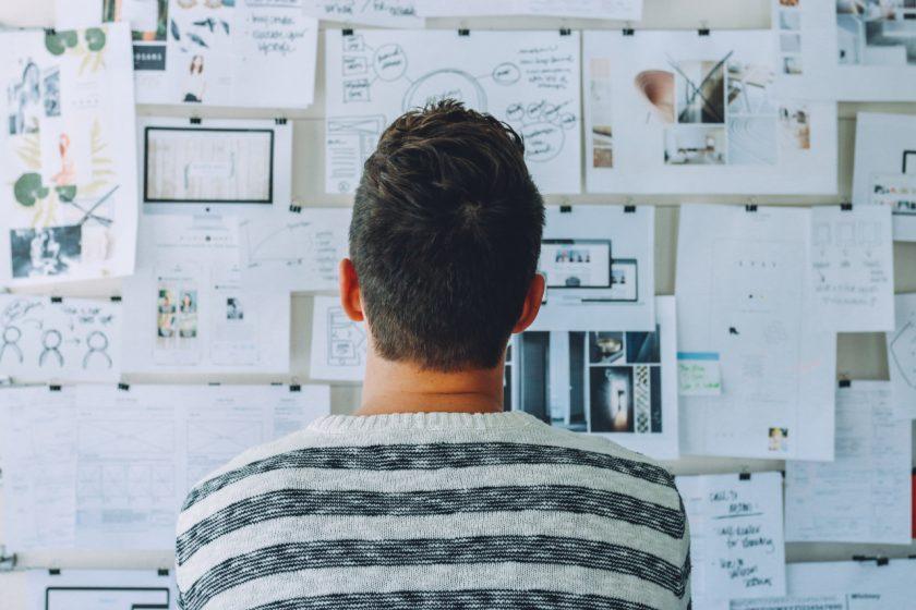 壁に貼ったたくさんの紙を眺める男性