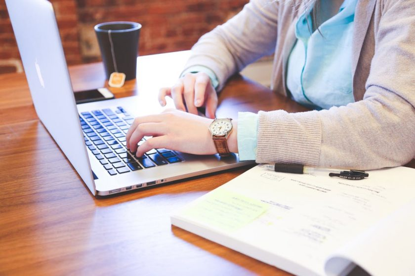 本を開きながらノートパソコンで仕事をする女性