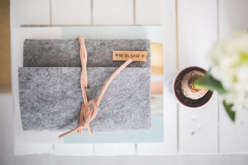 白いテーブルに置かれた花とノート