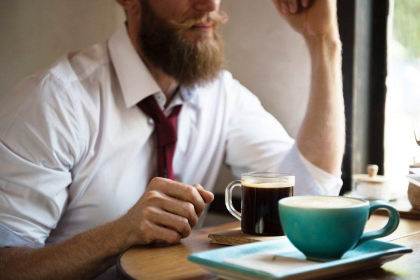 コーヒーを飲みながら話し合いをしている男性