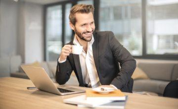 休憩中にコーヒーを飲む笑顔の男性