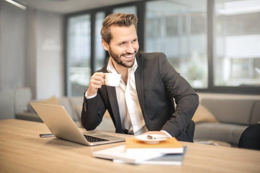 休憩中にコーヒーを飲む笑顔の英語ネイティブスピーカーの男性講師