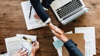 テーブルの上で握手をかわすビジネスマン