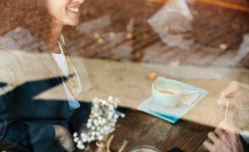カフェのガラス越しに見える笑顔の女性