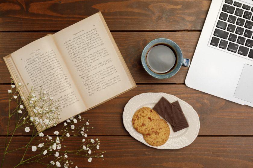 テーブルの上のノートパソコンと本と花とコーヒーにクッキー