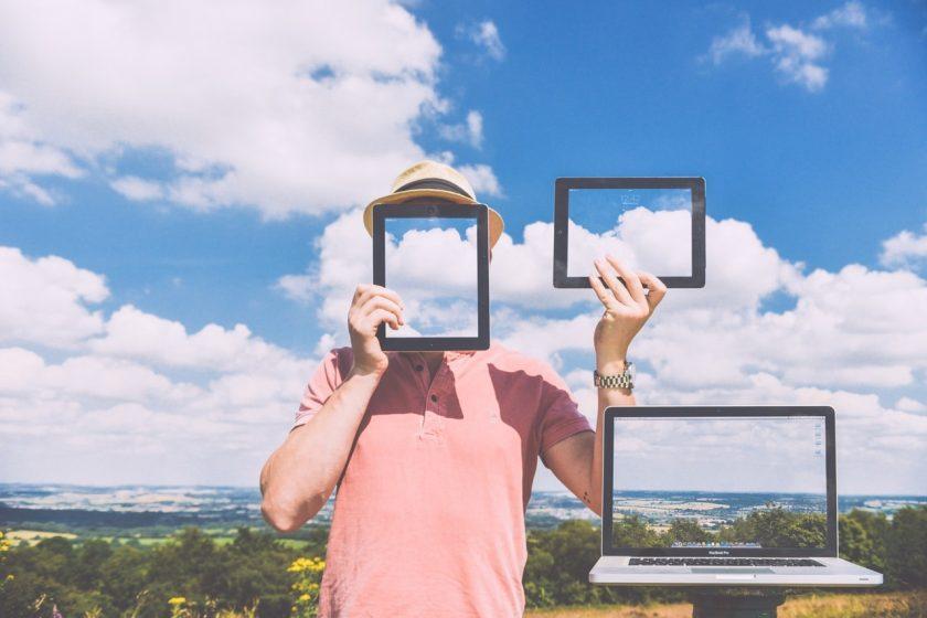 見晴らしのいい丘で青空を写したPCとタブレットを持つ男性