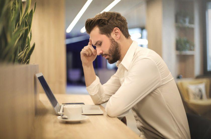 パソコンの前で肘をついて悩む男性の横顔