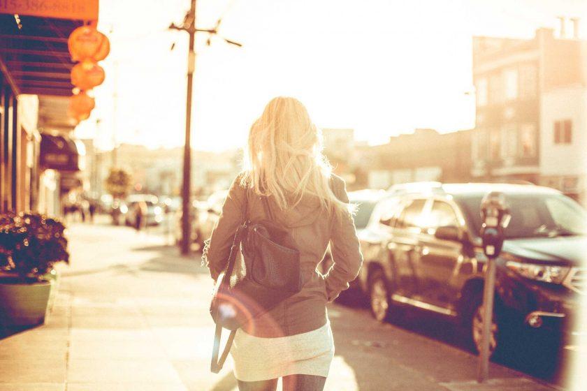 眩しい日差しの中を歩く外国の女性の後ろ姿