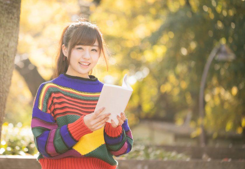 公園で本を読むカラフルな服を着た女の子