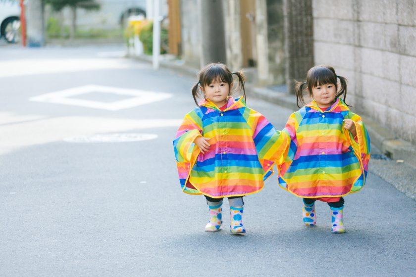 虹色ポンチョを着て手を繋ぐ双子の少女
