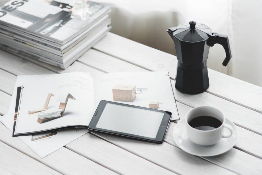 白いデスクの上の雑誌とコーヒーとポット