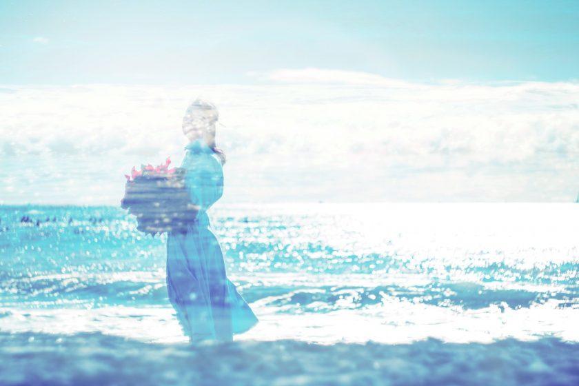 きらめく海の風景に重ねて透かした花を抱える女性