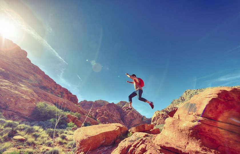 広大な岩場をジャンプしている男性