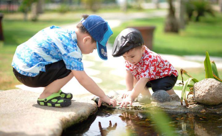 水辺に手を伸ばす2人の男の子
