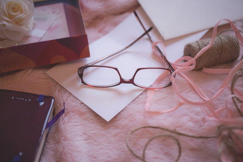ピンクのラグの上に散らかった眼鏡や小物