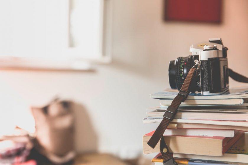 山積みになった本の上に置かれたカメラ
