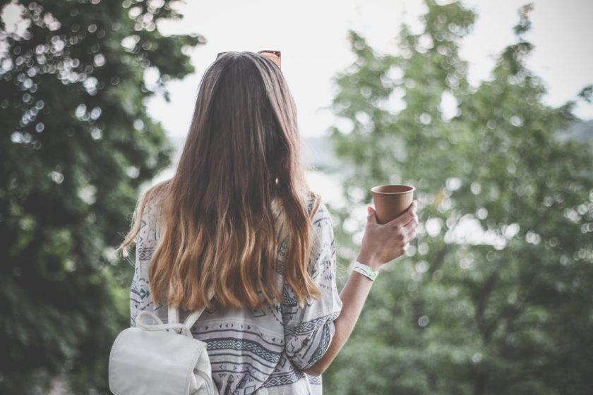 森の中でコーヒーを片手に持つ女性の後ろ姿