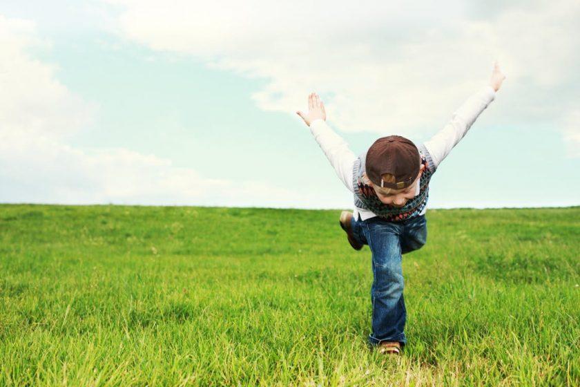 両手を後ろに広げて飛行機のポーズで草原を走る男の子
