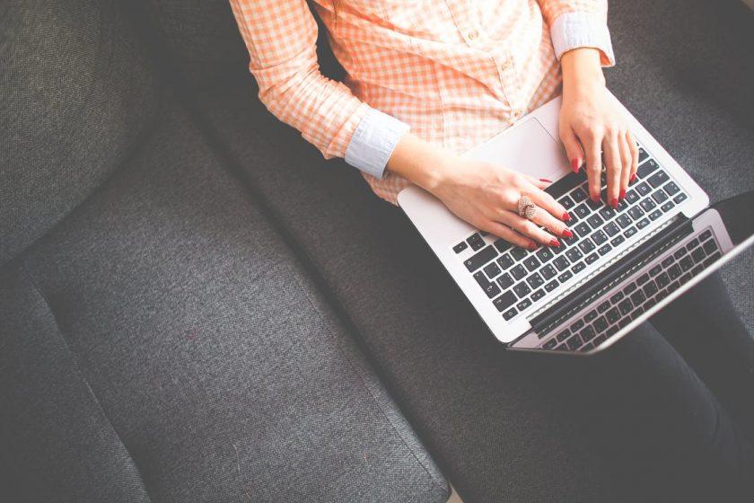 ノートパソコンを膝に乗せてタイピングする女性