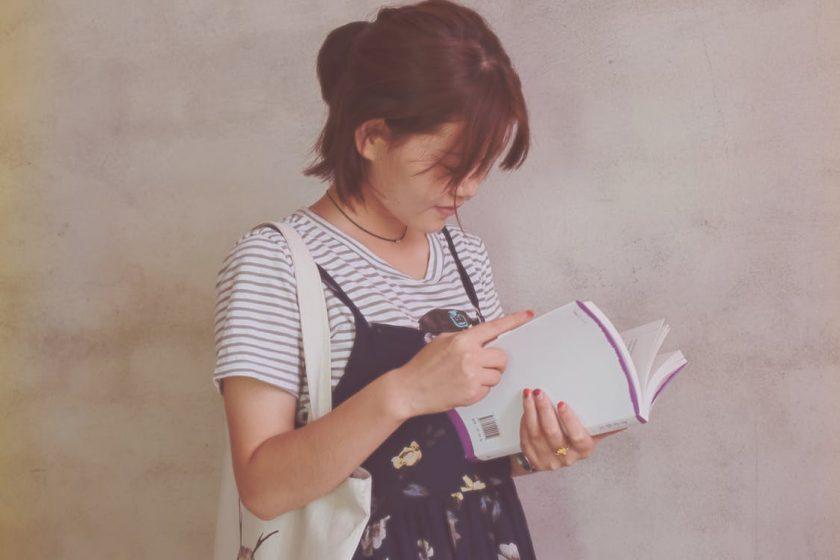 立って本を読む女性