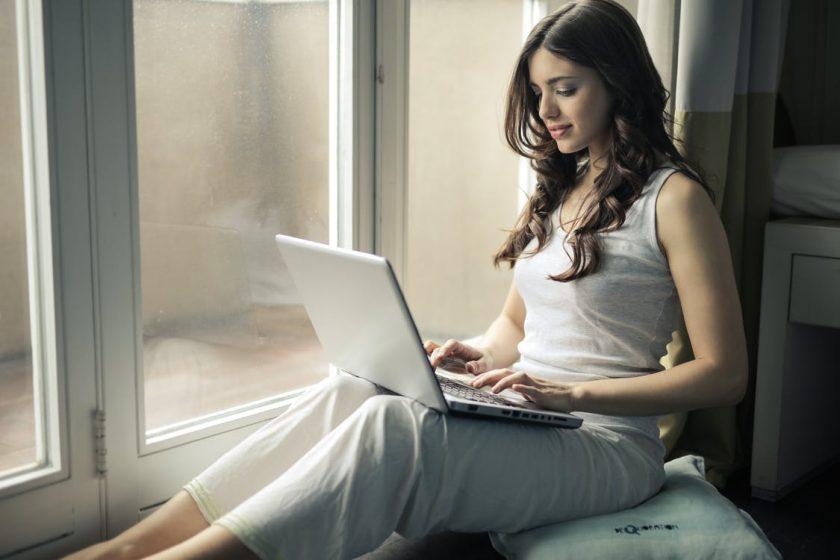 窓辺で膝にノートパソコンを乗せる女性