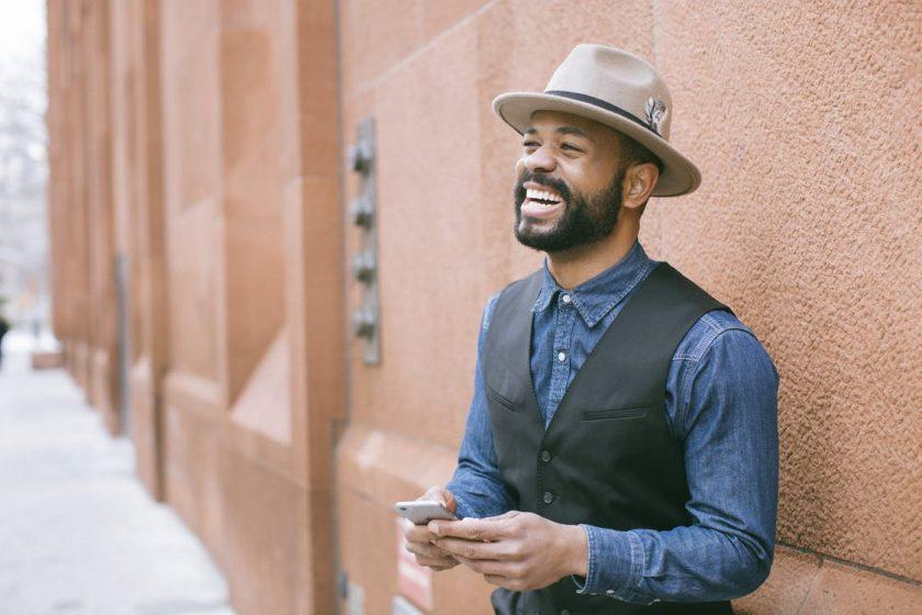壁際でスマホを持つ笑顔の黒人男性