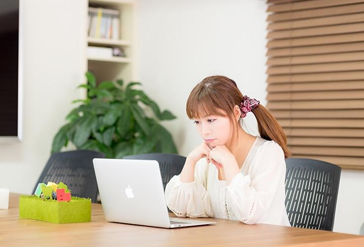 パソコンに向かってオンライン英会話レッスンを受ける主婦