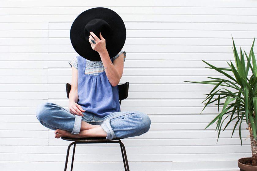 白い壁の前で椅子に座る外国人女性