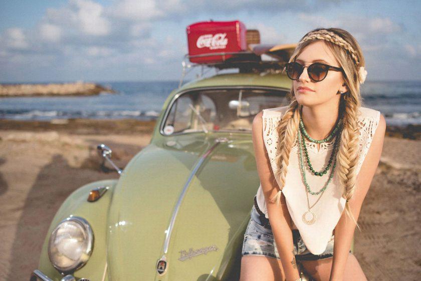 ビーチに止めたかわいい車のボンネットに腰掛ける綺麗な白人女性