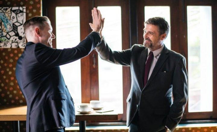 笑顔でハイタッチを交わす2人のビジネスマン