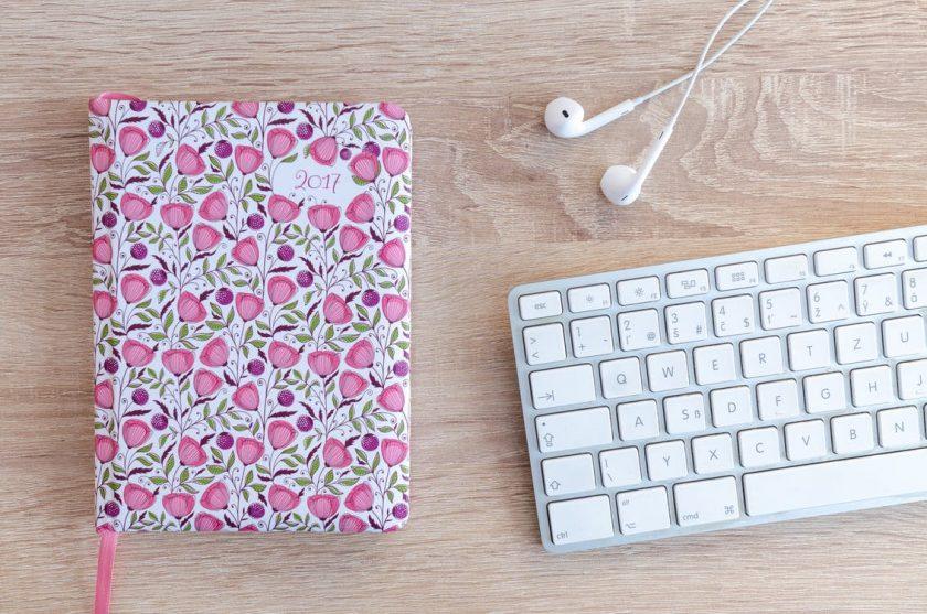ピンクの花が散りばめられたカラフルな日記とキーボード