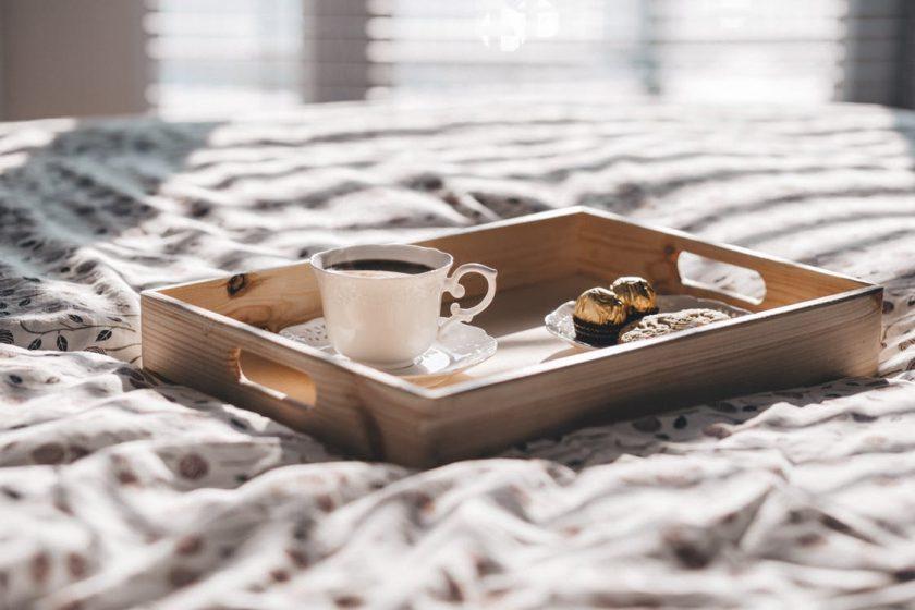 ベッドの上に置かれたトレーに乗ったコーヒーとお菓子
