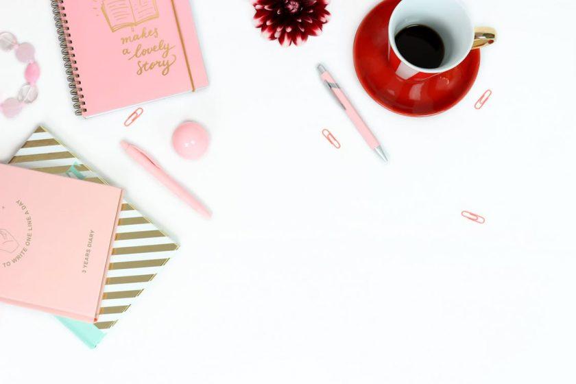 赤いティーソーサーに乗ったコーヒーとピンクのノートとペン