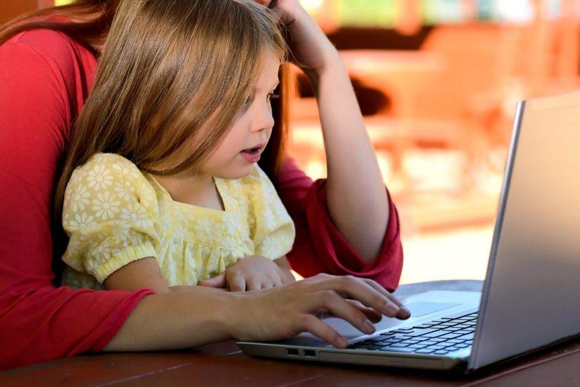 お母さんと一緒にパソコンを見る少女