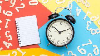 カラフルな画用紙の上に置かれた目覚まし時計とメモ